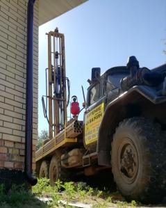 Скважина может располагаться даже в 1 метре от дома - все зависит от того, насколько близко к зданию может подобраться бурильная техника